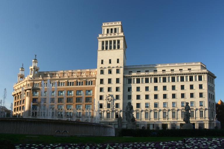 Barcelona, Plaza de Cataluna - Edificio Banesto (Banco Español de Crédito). De estilo neoclásico situado en mitad de la Plaza Catalunya, albergó el célebre Hotel Colón y durante la Guerra Civil española alojó a los miembros del PSUC. Después pasó por las manos de Banesto y Cajamadrid (de donde coge el nombre). Aunque originalmente se construyó en 1902, con ampliaciones en 1916, no fue hasta 1942 que el arquitecto Eusebi Bona Puig lo rediseñó tal y como lo conocemos hoy.